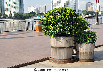 Wooden plant-pots put on floors beside river.