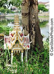 shrine of the household god beside tree.