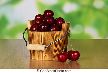 Wooden bucket filled with cherries - Heap of ripe sweet...