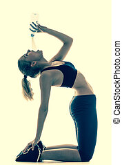sporty woman doing stretching exercise drinking water - Full...