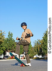 Skateboarding Fun - Smiling teenage boy with his thumbs up...