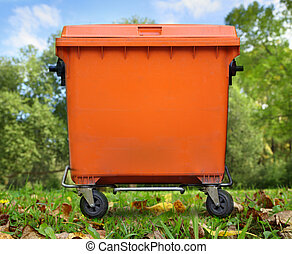 Orange garbage bin on foliage