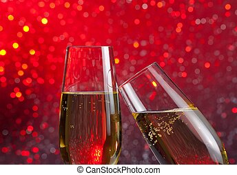 two champagne flutes with gold bubbles on red light bokeh...