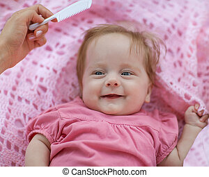 Mother combing red hair newborn girl