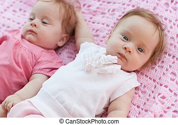Sweet little twins lying on a pink blanket They in pink and...