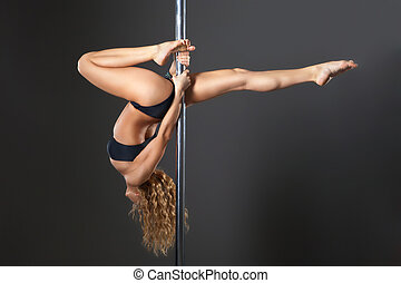 Attractive sexy woman pole dancer performing against grey...