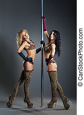 Two young sexy women exercise pole dance against a dark...