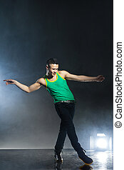 Dancer posing on background with flashes and smoke - Modern...