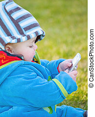 Colourful baby boy playing with cell phone - Colourful baby...
