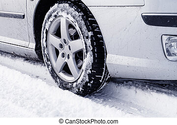 Winter tyre - Close up of a cars tires on a snowy road -...