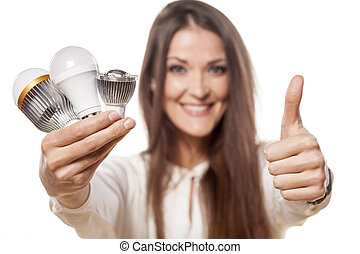 LED concept - smiling girl holding a LED bulb in one hand...