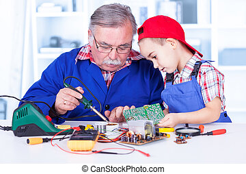 Grandfather explaining to grandchild how soldering works and...