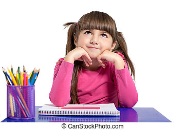 isolated little girl in a pink shirt is sitting at the table with colored pencils