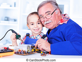 Happy grandfather and grandchild working together in...