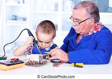 Grandfather teaching grandchild working with soldering iron...