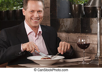 Businessman eating. Confident men in formal wear eating at...