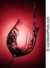 Red wine being poured into wine glass against red background