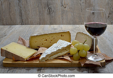 different french cheese tray with a glass of wine