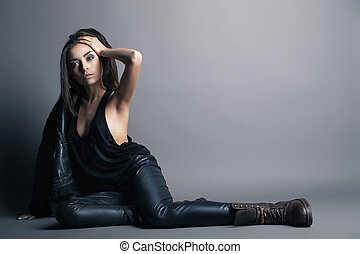Fashion model wearing leather pants and jacket posing on...