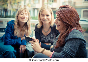 three friends woman at the bar using phone in urban contest