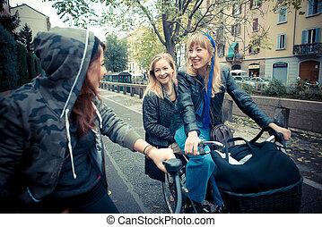 three friends woman on bike in urban contest