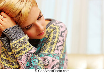 Closeup portrait of young depressed woman at home