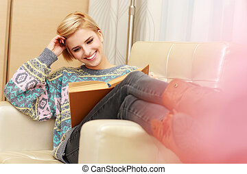 Young happy woman reading a book on the armchair at home