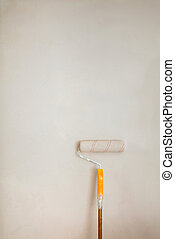 Roller brush with orange grip against wall.