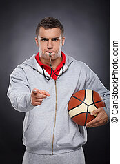 Displeased trainer. Portrait of angry young coach whistling...
