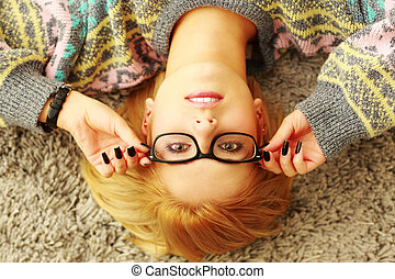 Portrait of a young woman putting her glasses on