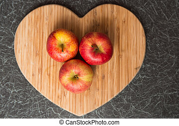 Three red apples on Heart Shaped Chopping Board - Three red...