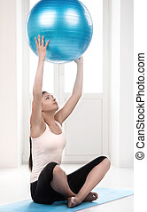 Playing with fitness ball Beautiful young women exercising...