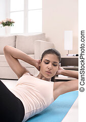 Doing her exercises at home. Confident young women...