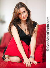 Woman on couch - young beautiful woman in the room on a red...