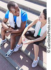 After the training. Young interracial couple sitting at stairs and talking after the training