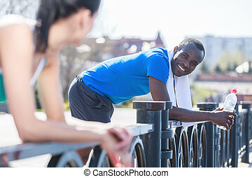 Couple relaxing after jogging. Young interracial couple standing in distance and looking at each other after outdoor jogging