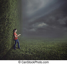 Woman reading on surreal landscape.