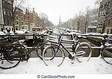 Amsterdam covered with snow with the Westerkerk in winter in...