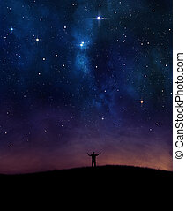 Night sky praise - A man lifting his hands in praise under...