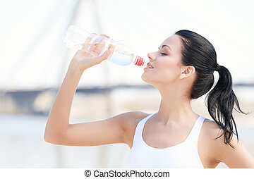 I need some water after training. Portrait of beautiful young woman drinking water after training