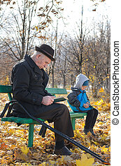 Retired man reading in the park with his grandson - Retired...
