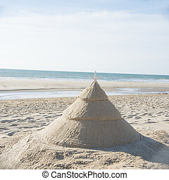 Christmas tree on beach made out of sand with starfish as...