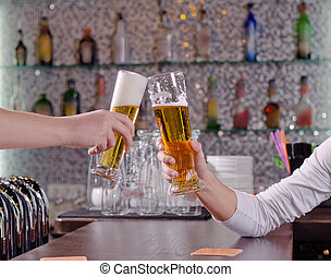 Two men toasting each other with their beers clinking their...