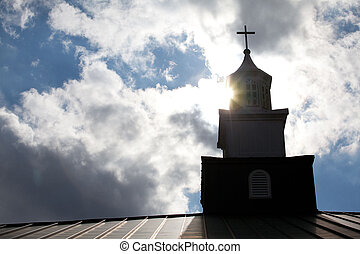 Church steeple with bright sun and clouds in the sky.