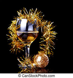 Glass with drink, a Christmas ball and tinsel - Glass with...