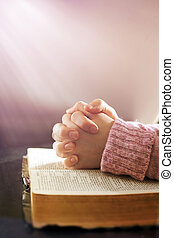 Woman praying - Womans hands in prayer over an open Bible