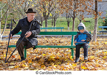 Elderly handicapped man watching a young boy - Elderly...