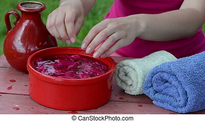 bowl blossom spa - girl dip the hands in a red clay bowl...