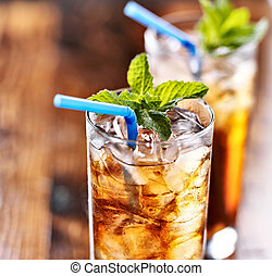 iced tea with blue straw and mint garnish