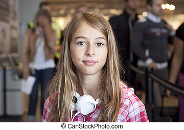 Teenage girl in airport travelling - A young woman sitting...